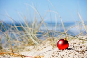 red christmas ornament in sand