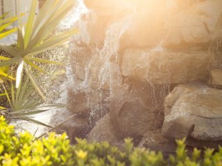 Rock waterfall with lens flare and sunshine.